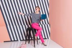 Überraschte stilvolle Frau mit einem Laptop in ihren Händen in einem gestreiften T-Shirt und in rosa Hosen, Lebensstil, Blogger,  Stockbild