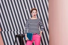 Überraschte stilvolle Frau mit einem Laptop in ihren Händen in einem gestreiften T-Shirt und in rosa Hosen, Lebensstil, Blogger,  Stockfotografie
