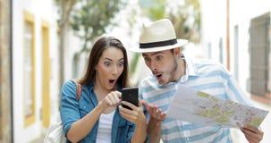 Überraschte Touristen, die im Urlaub on-line-Handel finden stock video footage