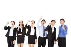 Überraschte und überraschte Geschäftsleute, die oben schauen und zeigen Stockbild