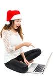 Überraschte Weihnachtsfrau, die auf ihren Laptop zeigt Stockbild