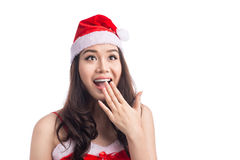 Überraschte Weihnachtsfrau, die einen Sankt-Hut lokalisiert auf Weiß trägt Stockbild