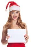 Überraschte Weihnachtsfrau, die einen Sankt-Hut trägt stockbilder