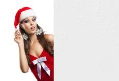 Überraschte Weihnachtsfrau in Sankt-Hut, der leeres Brett hält Stockfotografie