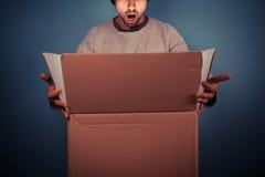 Überraschter öffnender aufregender Kasten des jungen Mannes Stockfotos