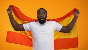 Überraschter afro-amerikanischer Sportfreund, der Spanien-Flagge, jubelnd für Sieg wellenartig bewegt zu stock video footage