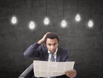 Überraschter Afroamerikanermann mit Zeitung, Ideen Lizenzfreie Stockbilder