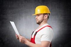 Überraschter Bauarbeiter, der Papiere hält stockfotos