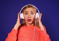 Überraschter blonder hörender Podcast Lizenzfreies Stockfoto