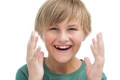 Überraschter blonder Junge mit den Händen oben lächelnd Lizenzfreie Stockfotografie