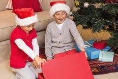 Überraschter Bruder und Schwester, die ein Geschenk öffnet Stockfotos