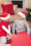Überraschter Bruder und Schwester, die ein Geschenk öffnet Stockbild