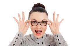 Überraschter Brunette, der ihre Gläser hält Stockfoto