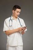 Überraschter Doktor, der Handy verwendet Stockfoto