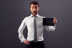 Überraschter Geschäftsmann, der den Tablette-PC zeigt Stockfoto