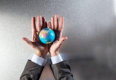 Überraschter Geschäftsmann, der die Erde für Berufsverantwortung und Strategie zeigt Lizenzfreie Stockfotografie
