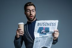 Überraschter Geschäftsmann in der Klage und Gläser, die eine Papierschale halten und Wirtschaftszeitung lesen lizenzfreie stockfotografie