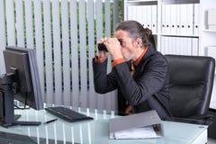 Überraschter Geschäftsmann, der mit Ferngläsern dem Schirm betrachtet Stockbilder