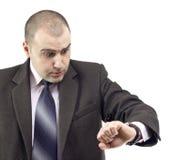 Überraschter Geschäftsmann, der seins Uhr konsultiert Lizenzfreie Stockbilder