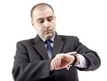 Überraschter Geschäftsmann, der seins Uhr konsultiert Stockfotos