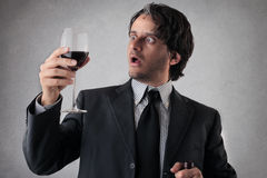 Überraschter Geschäftsmann mit einem Glas Wein Lizenzfreies Stockbild