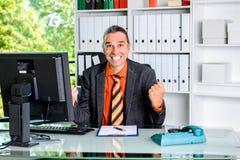 Überraschter Geschäftsmann an seinem Schreibtisch Stockbild