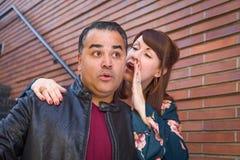 Überraschter hispanischer Mann und Frau, die Geheimnis flüstert stockbilder