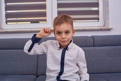 Überraschter Junge auf der Couch lizenzfreie stockfotos