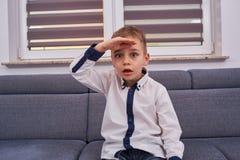 Überraschter Junge auf der Couch lizenzfreies stockbild