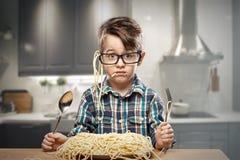 Überraschter Junge in den Gläsern mit Spaghettis Stockfoto