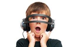 Überraschter Junge, der durch Kopfhörer schaut Stockbilder