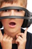 Überraschter Junge, der durch Kopfhörer schaut Lizenzfreies Stockfoto