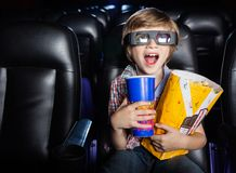 Überraschter Junge, der Film 3D im Theater aufpasst Stockfotografie