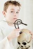 Überraschter Junge, der Schädel mit Stethoskop überprüft Stockbild