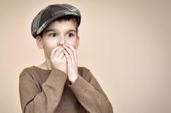 Überraschter Junge mit der Kappe, die seinen Mund mit den Händen bedeckt Lizenzfreies Stockbild