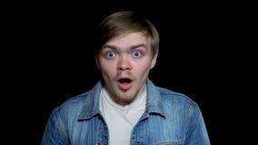 Überraschter junger, bärtiger Mann, der Mund offen beim Anstarren entlang der Kamera, lokalisiert auf schwarzem Hintergrund hält  lizenzfreies stockfoto