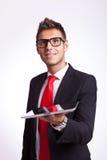 Überraschter junger Geschäftsmann, der eine Auflage anhält Stockfoto