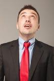 Überraschter junger Geschäftsmann, der oben schaut Lizenzfreie Stockfotografie
