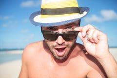 Überraschter junger gutaussehender Mann auf dem Strand Stockfotos