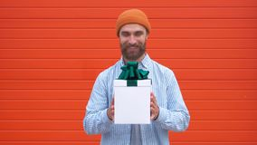 Überraschter junger Hippie-Mann mit dem Schnurrbart und Bart in der Überraschung, die weißen Kasten mit Geschenken auf einem rote stock video footage