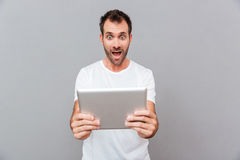 Überraschter junger Mann, der Tablette über grauem Hintergrund hält Lizenzfreie Stockbilder