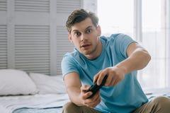 Überraschter junger Mann mit dem Steuerknüppel, der Videospiel beim Sitzen spielt lizenzfreie stockfotos