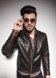 Überraschter junger Modemann, der seine Sonnenbrille entfernt Lizenzfreies Stockfoto