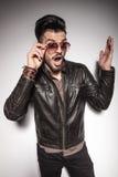 Überraschter junger Modemann, der seine Sonnenbrille repariert Lizenzfreie Stockbilder