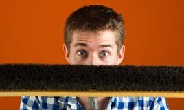 Überraschter kaukasischer Mann, der hinter Besen sich versteckt Stockbild