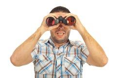 Überraschter Kerl, der binokulares untersucht Lizenzfreie Stockbilder