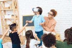Überraschter kleiner Junge steht in den Gläsern der virtuellen Realität im Grundschuleklassenzimmer stockfotos