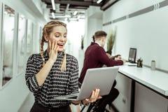 Überraschter leicht-haariger weiblicher Büroangestellter, der während des Gespräches ausdrucksvoll ist lizenzfreie stockfotos