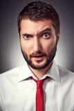 Überraschter Mann über grauem Hintergrund Stockfotografie