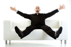 Überraschter Mann auf Couch Stockfotografie
